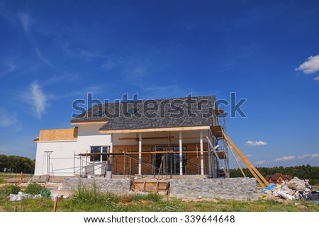 New Cozy House Building Construction Exterior. Cozy house with Dormers, Skylights, Ventilation, Gutter, Drainage, Plastering and Using Color. Outdoor. - stock photo