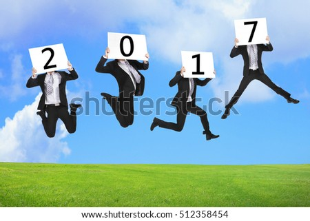 2017 new year business concept, Business man happy holding billboard and jumping or running on the green grass
