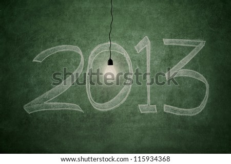 2013 new year concept: an electric light bulb glowing bright in front of blackboard symbolizing good year - stock photo