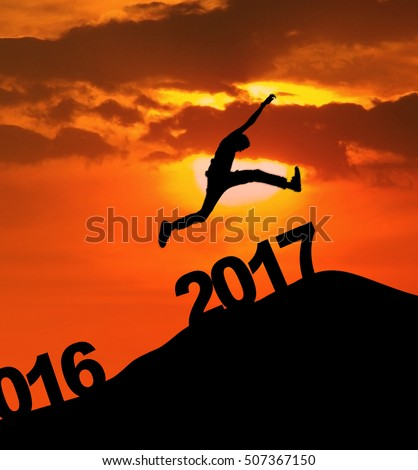 2017 New year concept: Silhouette of a  man jumping over the  numbers 2017 on the hill during sunset or sunrise