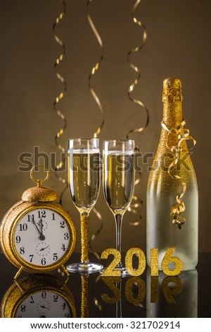 2016 New Year concept with the date in numbers, an elegant flute and bottle of champagne - stock photo