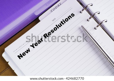 """New Year Resolutions"" text on notebook on a wooden table with open diary and pen - conceptual images - stock photo"