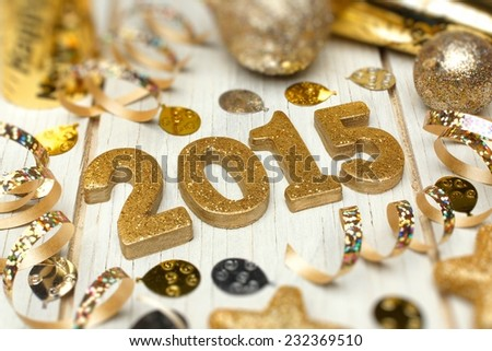 2015 New Years Eve golden numbers with confetti and decorations on a white wood background       - stock photo