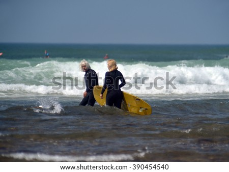 NEW YORK-JUNE 13: Unidentified man and woman surfers with surfboard on Ditch Plains surfing beach go to surf in Montauk, New York in the Hamptons on June 13, 2015.