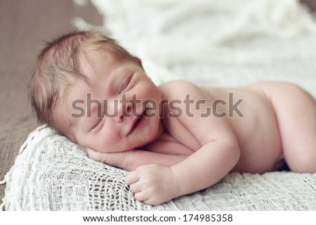 Newborn baby boy giving you a big smile - stock photo