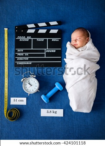 newborn baby lying on blue blanket with symbolic personal data of birth - stock photo