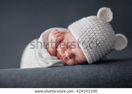 Newborn baby 2 weeks old sleeping on soft blue  fluffy blanket with funky woolen hat - stock photo