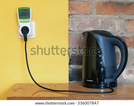 NICA, LATVIA - NOVEMBER 6, 2015: Electric teapot is connected with socket through digital electricity consumption meter for energy saving.
