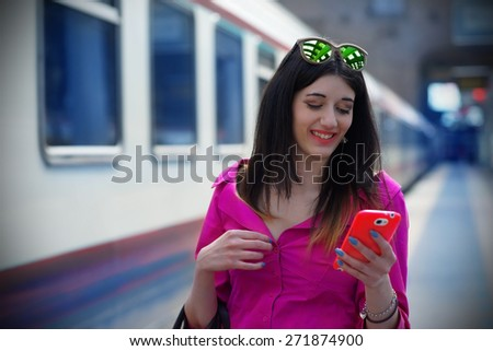 Nice Girl at the Train Station with her Smartphone                            - stock photo