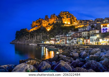 Night in Parga, Greece. A view at fortress, houses and boats near the rocky coast. - stock photo
