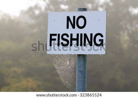No Fishing sign in the the mist with cobweb