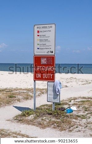 """No Lifeguard On Duty"" and ""Beach Warning Flags"" signs at the beach, Florida."