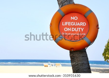 """No lifeguard on duty"" sign on the beach - stock photo"