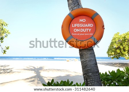 """""""No lifeguard on duty"""" sign on the beach - stock photo"""