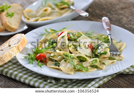 Noddles stuffed with spinach and quark (a South Tyrolean specialty so-called  'Schutzkrapfen') served with rucola butter sauce - stock photo