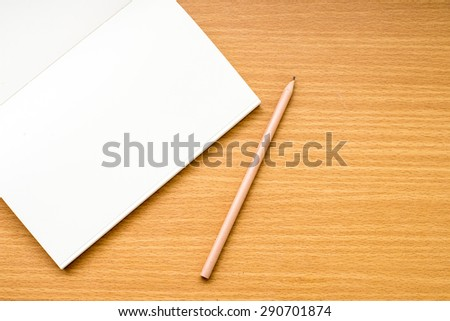 Note book with pencil on a wooden desk - stock photo