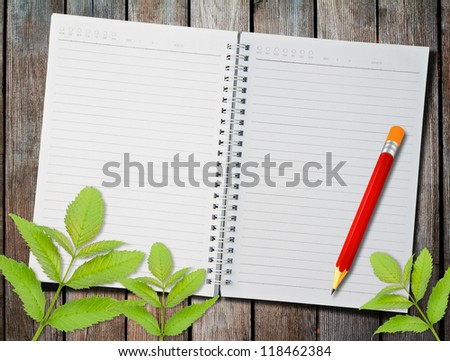 notebook and pen on the table with green leaves