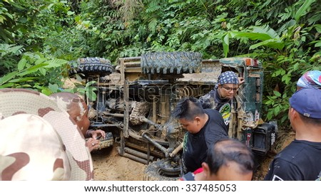 10 November 2015 , Raub, Malaysia, Group of fourwheller try to help car skidded and overturned in slippery road in Sungai Liang Advanture Trail