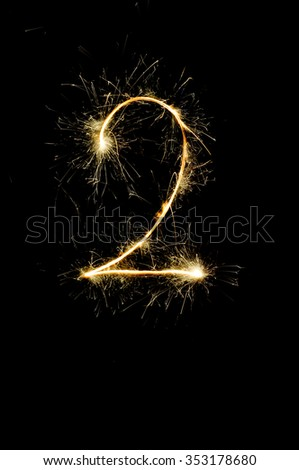 """2"" number drawn with bengali sparkles isolated on black background,number from sparkler on black background"