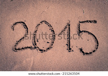 2015 number written into sand on beach
