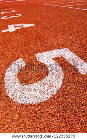 """Numbers """"5"""" on running track at arena. - stock photo"""
