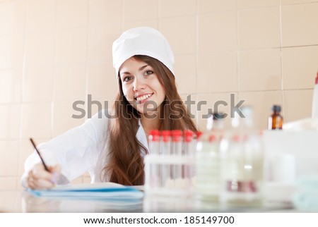 nurse working in medical laboratory. Model signs the model release - stock photo