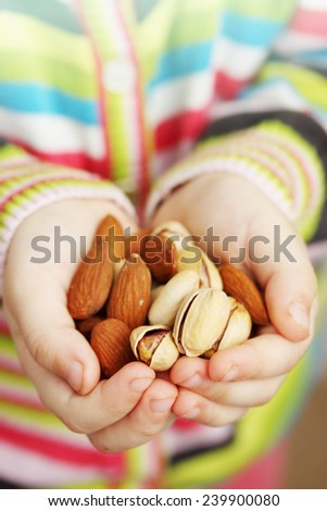 nuts, almonds and pistachios in children's hands - stock photo