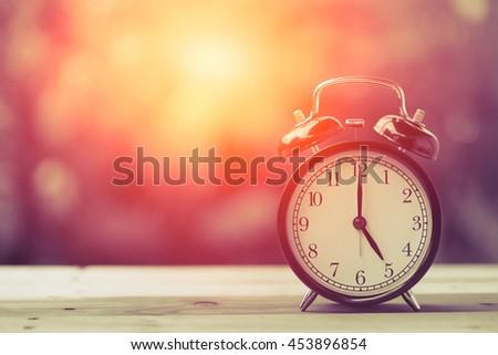 5 o'clock Clock Classic Vintage Retro Color Tone on Wood Table with Sun Light - stock photo