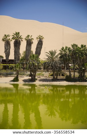 Oasis surrounded by sand dunes near Ica Peru - stock photo
