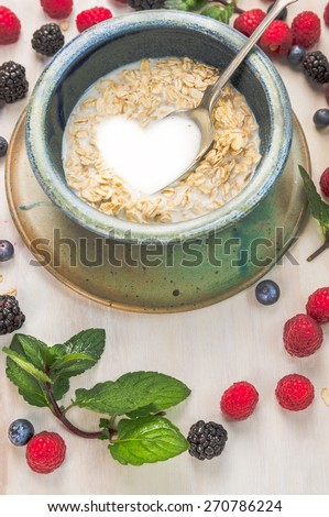 oat flakes with milk in a shape of heart on summer berries background - stock photo