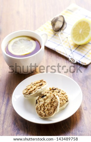3 oatmeal raisin cookies on white plate and cup of tea with lemon slice in it - stock photo