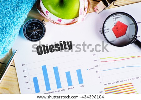 """Obesity"" black text on paper with magnifying glass on red spider bar on wooden table with compass, pen, towel, green apple with measurement tape, and whistles - fitness, diet and healthy concept - stock photo"
