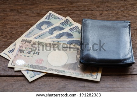 1000,10000 of Japan Yen on old wooden plank with wallet