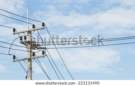 of telephone utility poles, cables, streetlights, and clear blue sky background - stock photo
