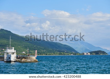 OHRID, MACEDONIA â?? 06 16 2016 : Fishing boat with the view of an snowy mountains and blue water in lake seascape