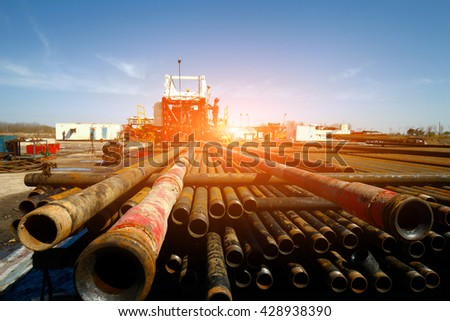 Oil pipe and oil drilling rig equipment - stock photo