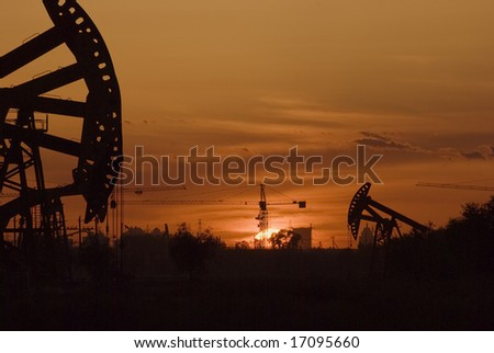 Oil rigs silhouette over orange sky-7