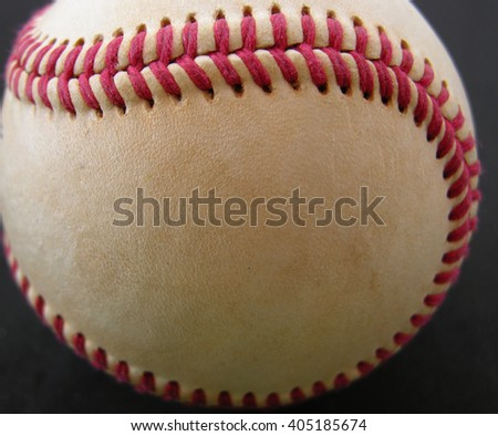 old baseball  shown close up and with some dirt on it.
