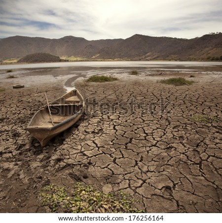 old boat on dry lake - stock photo