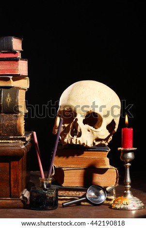 old books and skull over black - stock photo