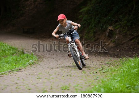 9 old boy riding his bike in park at speed. Blurred motion. Front view - stock photo