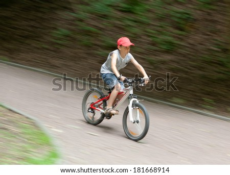 9 old boy riding his bike in park at speed. Blurred motion. Side view - stock photo