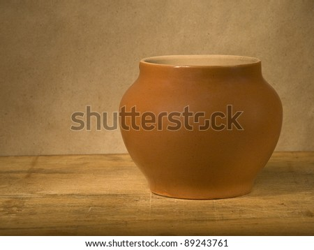 Old grunge clay pot on the old wooden table against gray wall. - stock photo