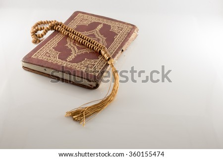 Old Islamic Book Holy Quran and beads on withe background