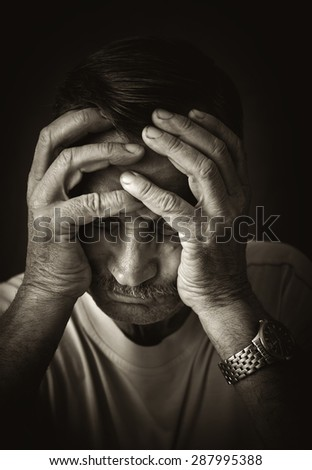 Old man put his head in his hands. - stock photo