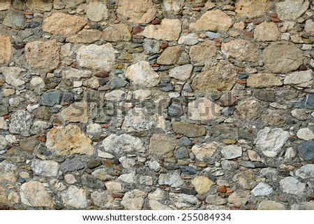 Old wall made of different varous, stones - stock photo