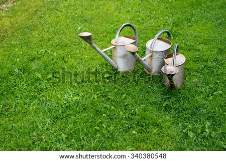 3 Old Watering can on meadow.