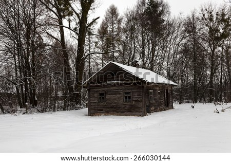 old wooden destroyed an abandoned house in the village in winter. - stock photo