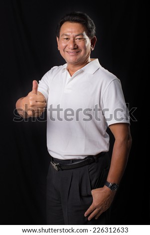 older man in a white t-shirt on a black background thumb up