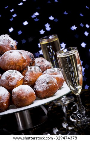 'Oliebollen', traditional Dutch pastry for New Year's Eve and two glasses of champagne. - stock photo